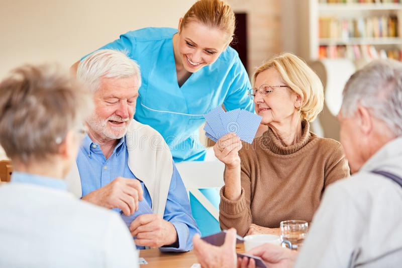 Nursing lady looks on while playing cards stock image