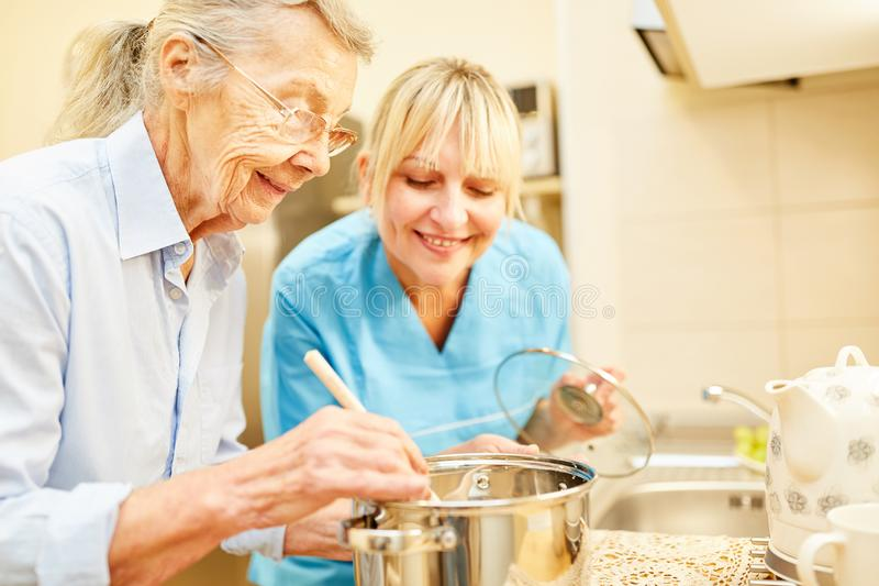 Nursing wife and senior citizen while cooking. Nursing wife and senior citizen in the kitchen while cooking in assisted living royalty free stock image