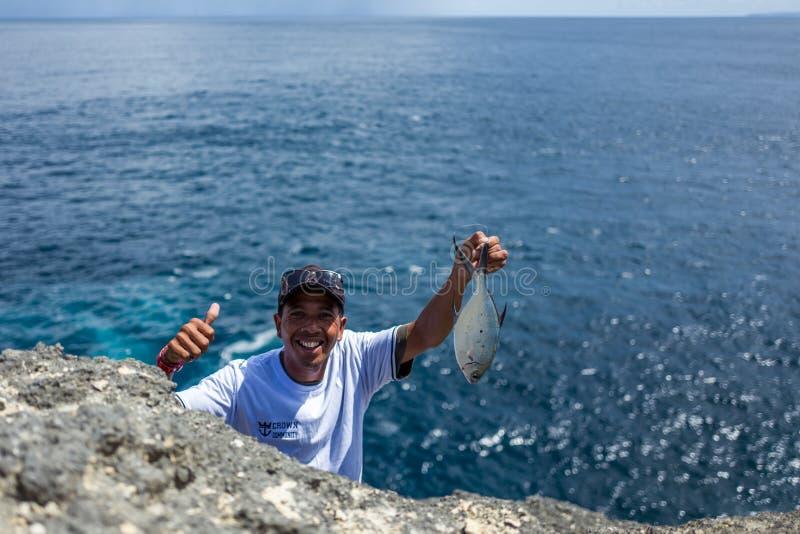 Nusa Penida, Indonesia - 22 marzo 2018: Un pescatore con il pesce che sorride alla macchina fotografica immagini stock libere da diritti