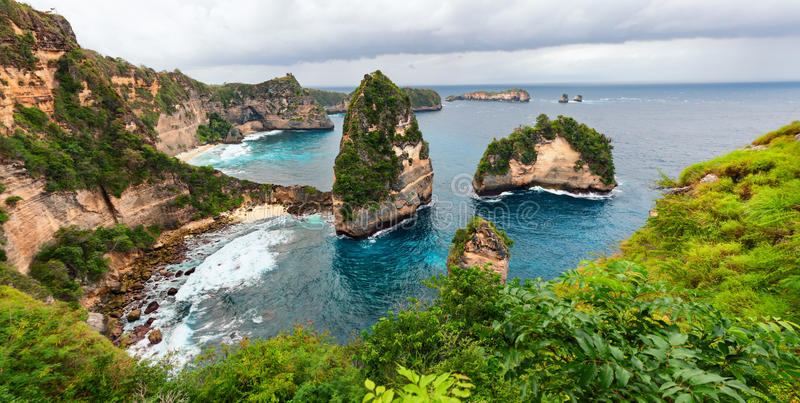 Nusa Penida island sea coast view. Sea coast view with little house standing on the high cliff bring above sea and little rocky islets. Atun beach, Nusa Penida stock photography