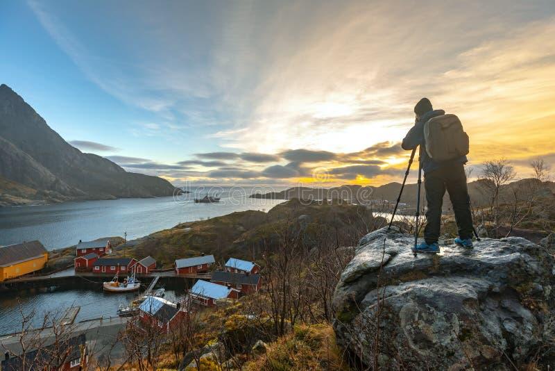 Nusfjord, Noruega - 17 de novembro de 2018: O turista toma uma paisagem da fotografia na aldeia piscatória de Nusfjord na municip fotografia de stock royalty free