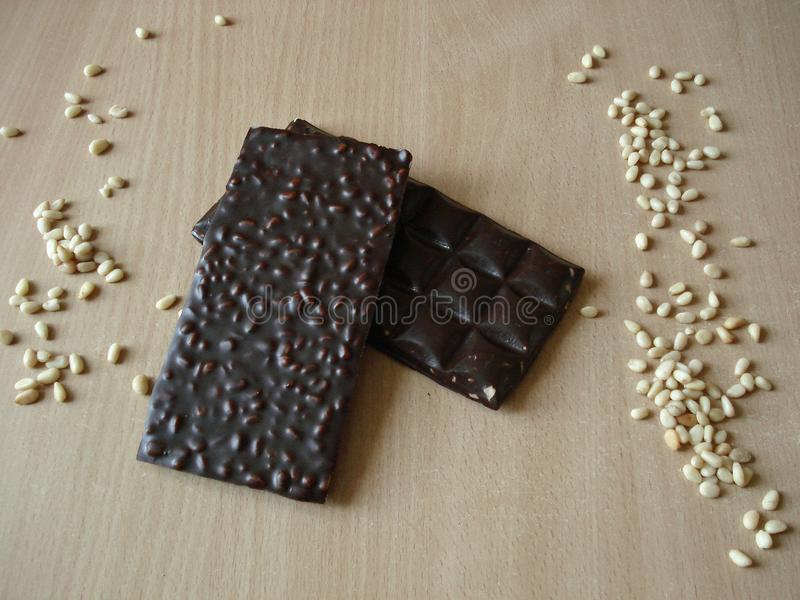 Bitter chocolate with pine nuts. Cedar nut near the chocolate bar. royalty free stock images