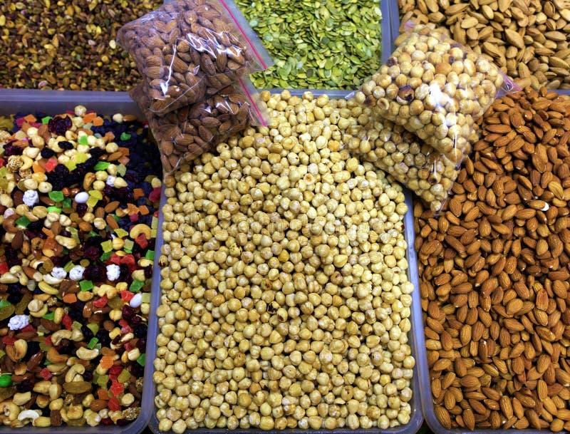 Kernels nuts in trays close up - hazelnuts, almonds, walnuts, cashews, pumpkin seeds in a blur. royalty free stock photo