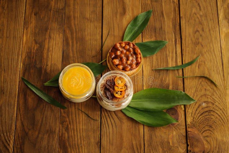 Nut tarts , tiramisu and lemon custard desserts on wooden background stock photos