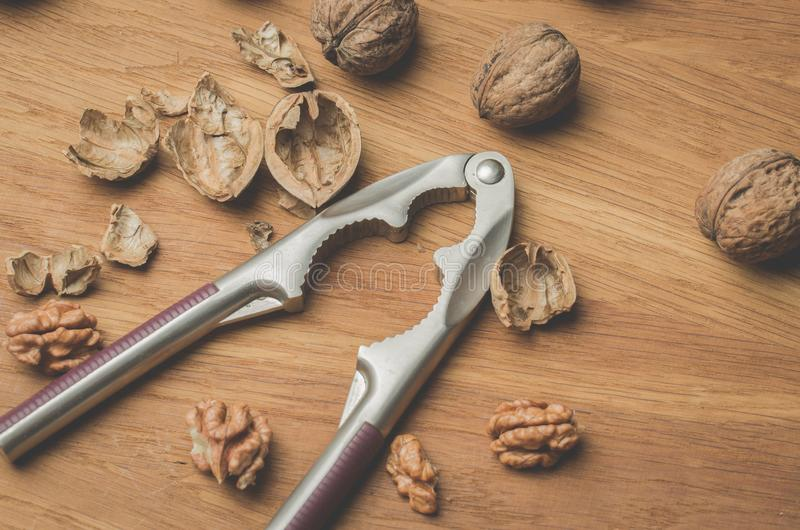 Nutcracker. Nutcracker and the split walnut on a wooden table. Top view. Walnuts, husks, background, kernel, food, healthy, natural, object, open, organic royalty free stock image