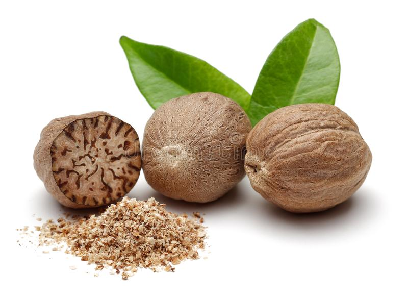 Nutmeg granules and nutmegs with leaves stock images