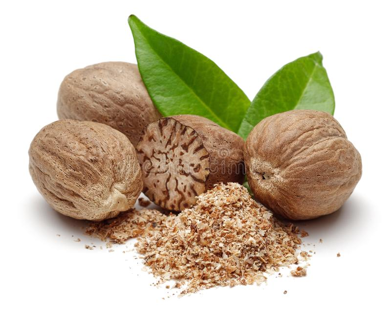 Nutmeg granules and nutmegs with leaves stock photo