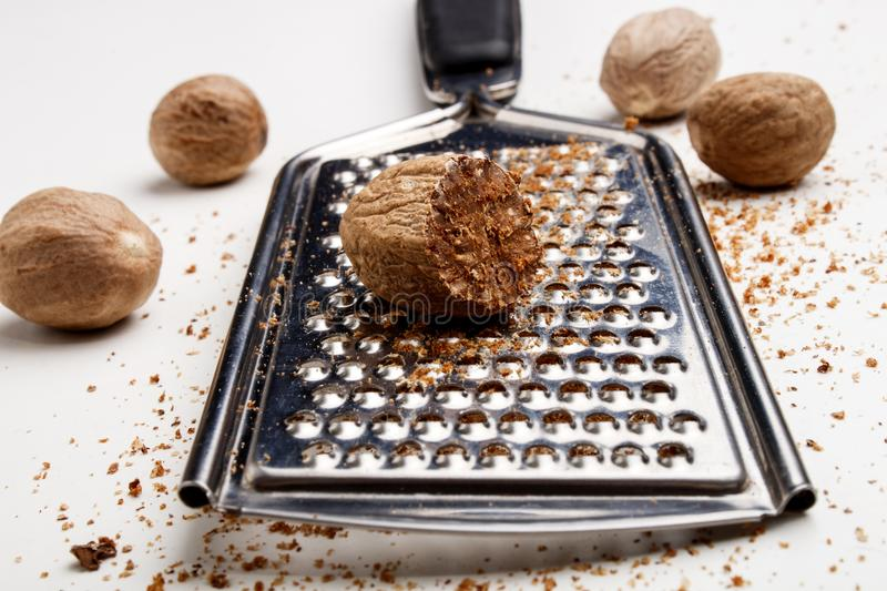 Nutmeg and powder on a grater. Nutmeg and powder on a metal grater stock photos