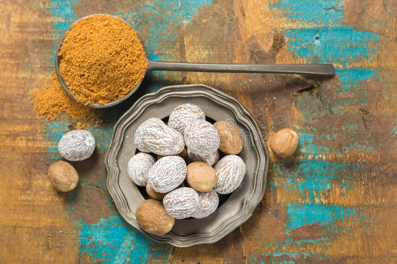 Nutmeg powder. Macro view whole nuts and grated muscat nuts. stock photos