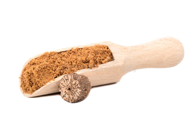 Nutmeg powder in scoop. Nutmeg powder in the scoop with a half walnut on white background stock image