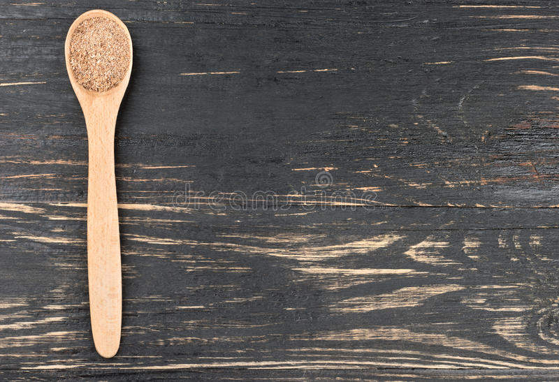 Nutmeg powder in spoon. Nutmeg powder in a spoon on an empty wooden background, top view royalty free stock images