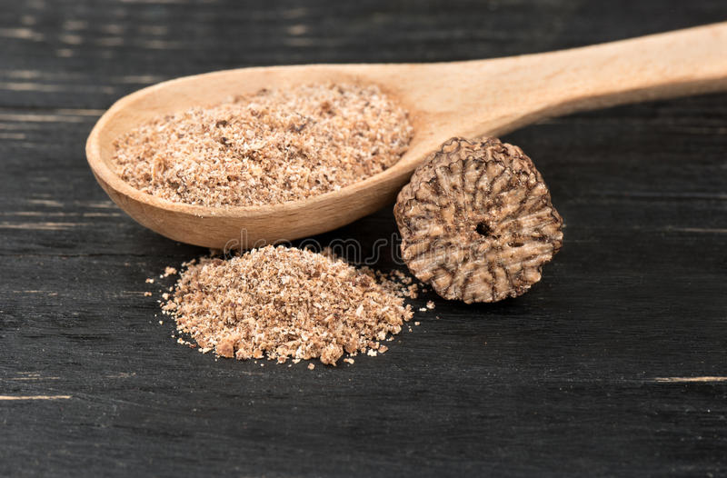 Nutmeg powder in spoon. Nutmeg powder in a spoon with a half of a walnut on wooden background royalty free stock photos