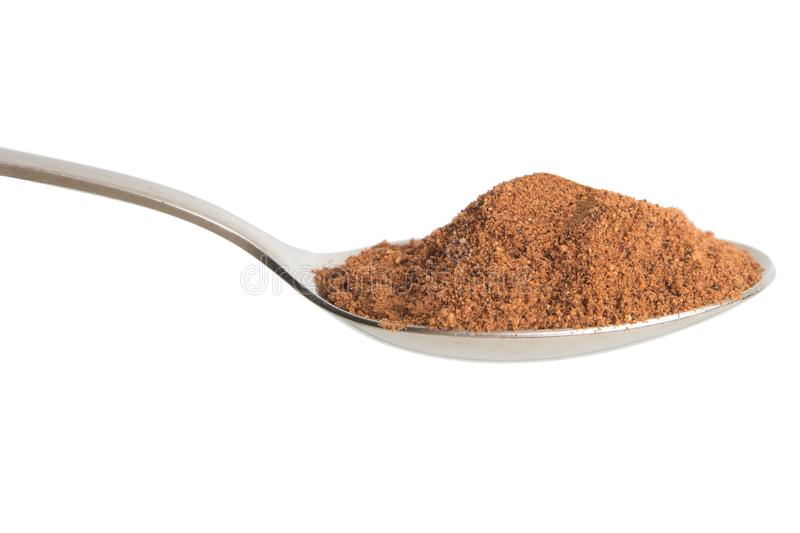Nutmeg powder in spoon. Isolated in white background stock photography