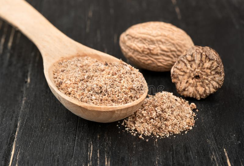 Nutmeg powder in spoon. Nutmeg powder in a spoon with a half of a walnut on wooden background royalty free stock images