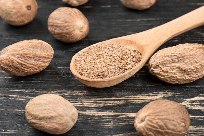 Nutmeg powder in spoon. Nutmeg powder in a spoon with scattered nuts on wooden background stock photography