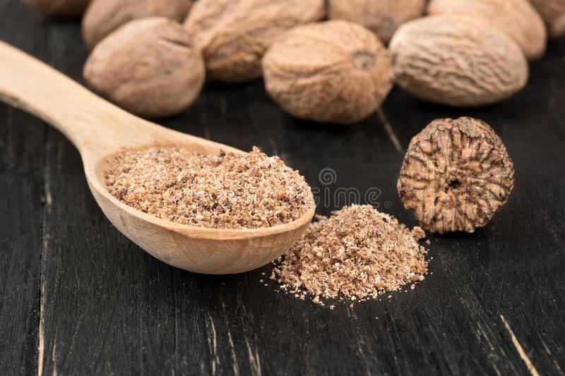 Nutmeg powder in spoon. Nutmeg powder in a spoon with scattered nuts on wooden background royalty free stock photography