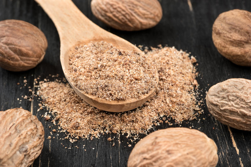 Nutmeg powder in spoon. Nutmeg powder in a spoon with scattered nuts on wooden background closeup royalty free stock photography