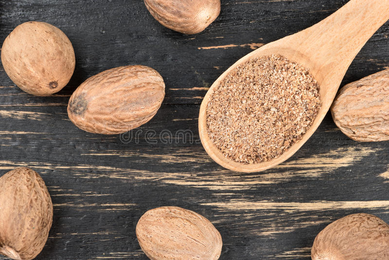 Nutmeg powder in spoon. Nutmeg powder in a spoon with scattered nuts on wooden background, top view royalty free stock photos