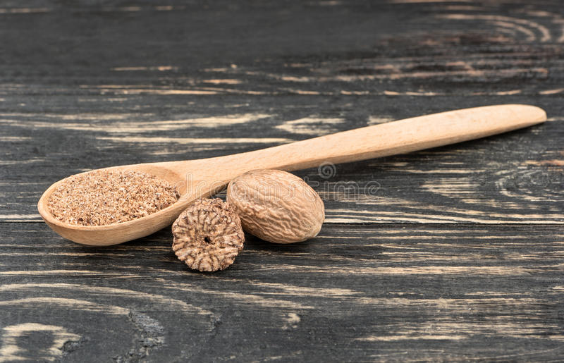 Nutmeg powder in spoon. On wooden background stock photo