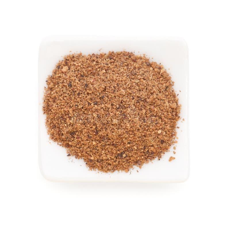 Nutmeg powder in a white bowl on white royalty free stock photography