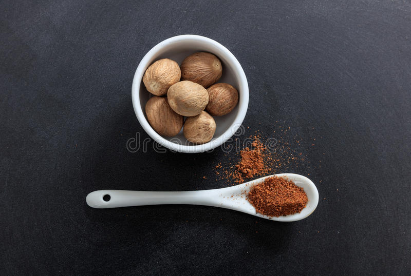 Nutmeg seeds and powder in porcelain bowl and spoon royalty free stock photos