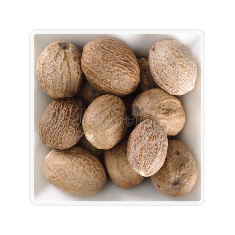 Nutmegs στο τετραγωνικό κύπελλο στο άσπρο υπόβαθρο στοκ φωτογραφίες
