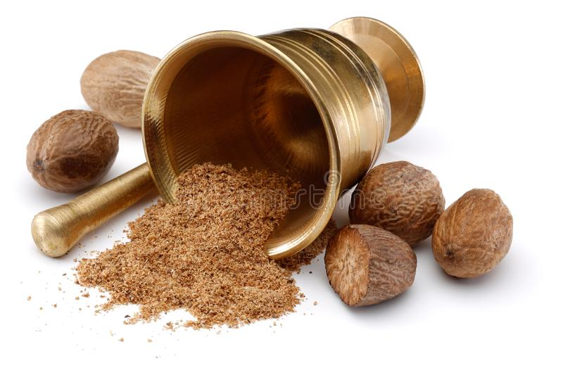 Nutmegs and nutmeg powder in bowl. Nutmegs and nutmeg powder in bronze bowl stock photos