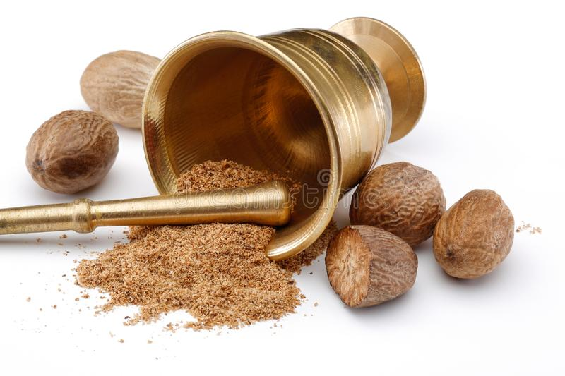 Nutmegs and nutmeg powder in bronze bowl. Isolated on white background royalty free stock image