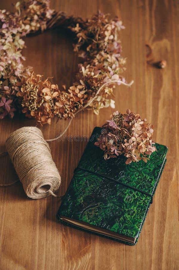 Nutowa książka z zieleni okładkowymi i wysuszonymi hortensjami na drewnianym stole obraz stock