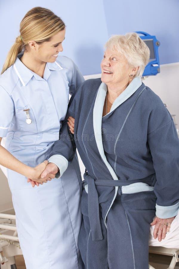 Nutra a mulher superior de ajuda fora da cama no hospital fotos de stock royalty free