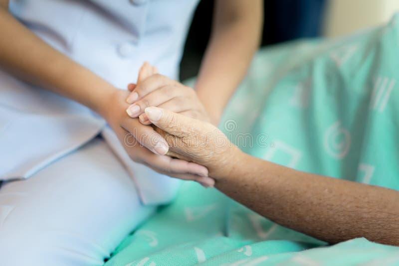 Nutra o assento em uma cama de hospital ao lado das mãos amiga de uma mulher mais idosa, cuidado para o conceito idoso foto de stock