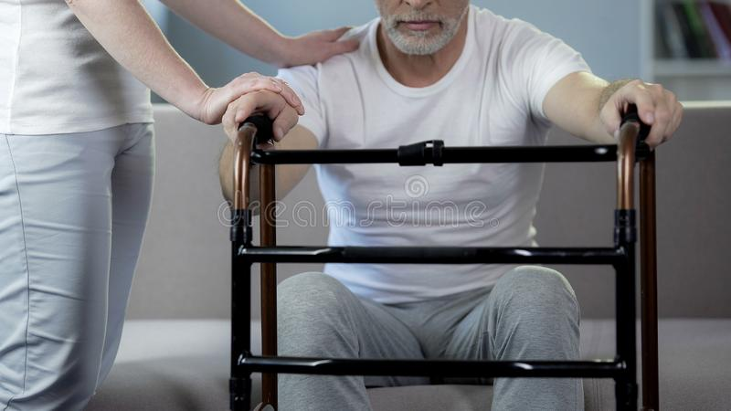Nutra o pensionista masculino de apoio que guarda o quadro de passeio, centro de reabilitação foto de stock royalty free