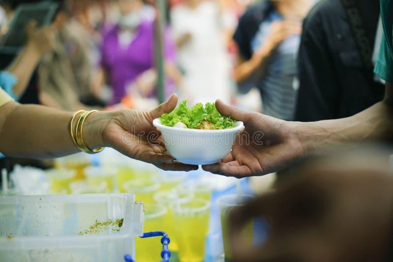 Nutrendo a mano al bisognoso nella società: Concetto di alimentazione: I volontari danno l'alimento al povero: donare l'alimento  fotografia stock
