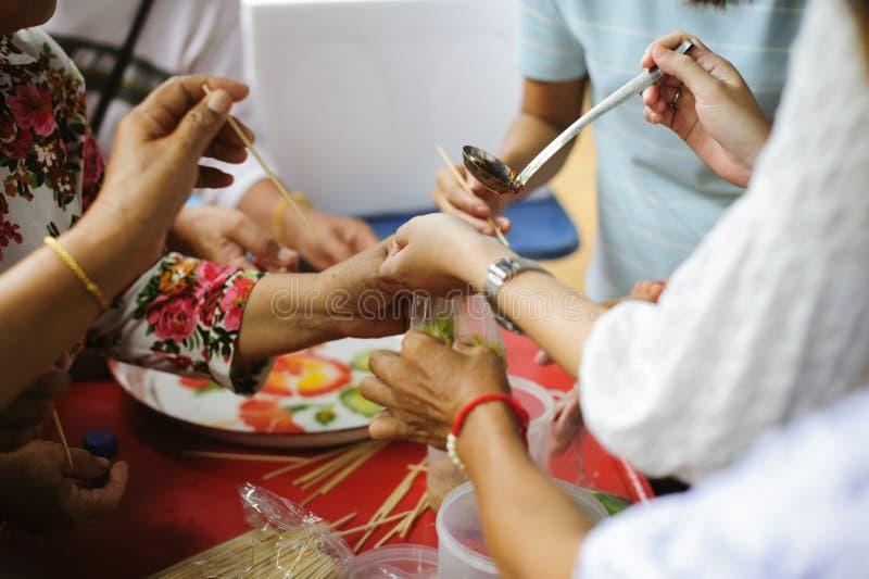 Nutrendo a mano al bisognoso nella società: Concetto di alimentazione: I volontari danno l'alimento al povero: donare l'alimento  immagine stock
