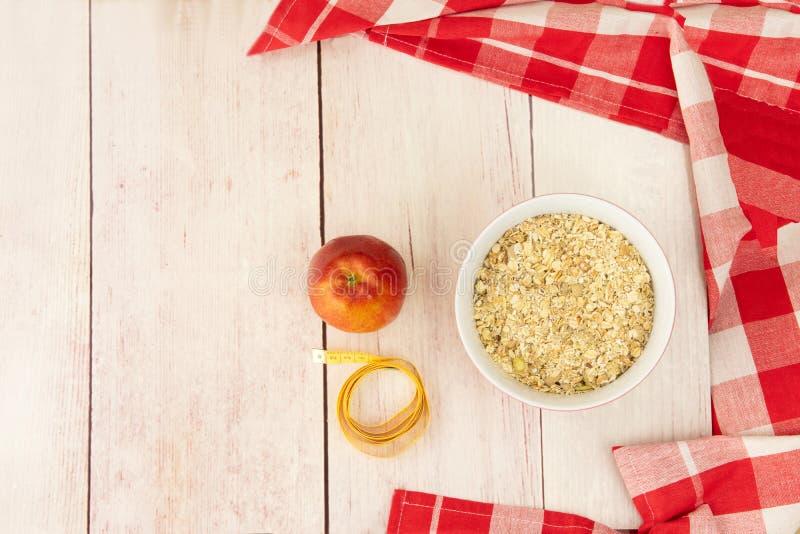 A nutrição e a dieta saudáveis com maçã e aveia lascam-se para perder wei fotos de stock