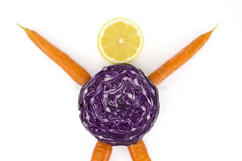 Nutrição e saúde da planta: cenouras para os braços e os pés, uma couve vermelha para o corpo e uma fatia de limão para a cabeça  imagens de stock royalty free