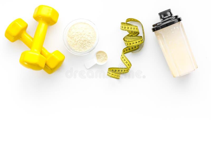 Nutrição para o crescimento do músculo A colher da proteína perto do abanador e o peso na opinião superior do fundo branco copiam imagens de stock
