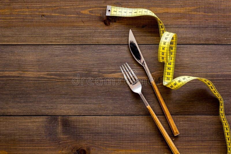 Nutrición apropiada para adelgazar La bifurcación, el cuchillo y la cinta métrica en la opinión superior del fondo de madera oscu foto de archivo libre de regalías