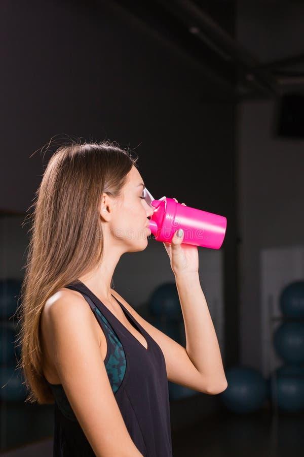 Nutrición de consumición de los deportes de la mujer muscular joven imagen de archivo