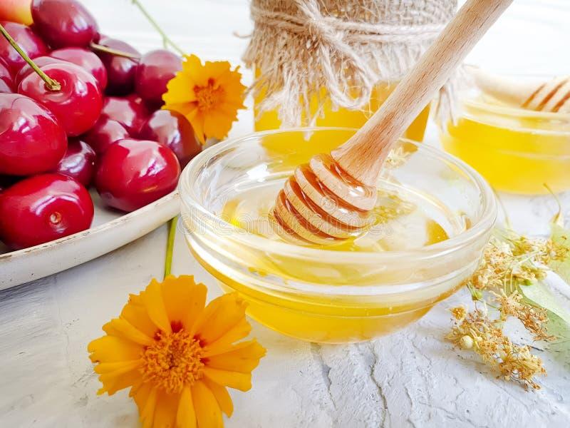 Nutrición natural deliciosa en un hormigón gris, postre de la cuchara de la cereza de la miel fresca de la baya imagen de archivo