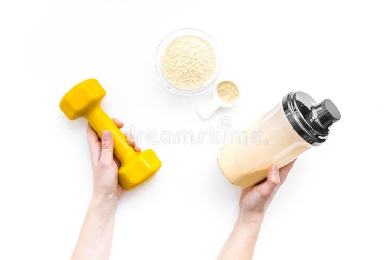 Nutrición para el crecimiento del músculo Cucharada de la proteína cerca de la coctelera y de la pesa de gimnasia en la opinión s fotografía de archivo