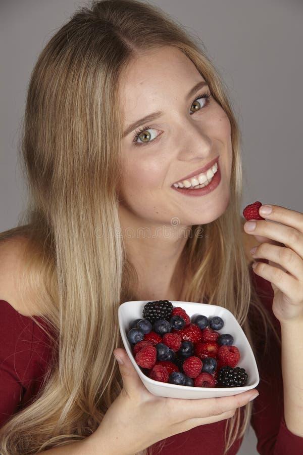 Nutrición sana - ella come un cuenco de ensalada de fruta foto de archivo