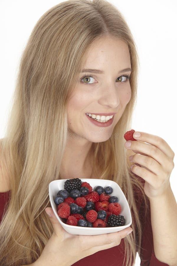 Nutrición sana - ella come un cuenco de ensalada de fruta fotografía de archivo