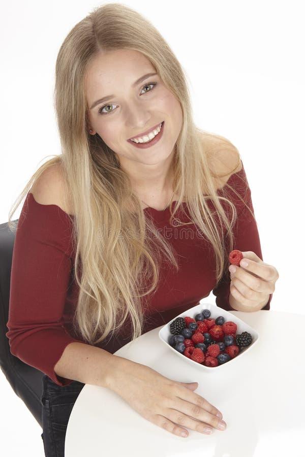 Nutrición sana - ella come un cuenco de ensalada de fruta fotografía de archivo libre de regalías