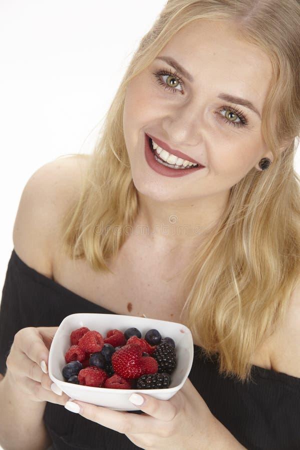 Nutrición sana - ella come un cuenco de ensalada de fruta imagenes de archivo