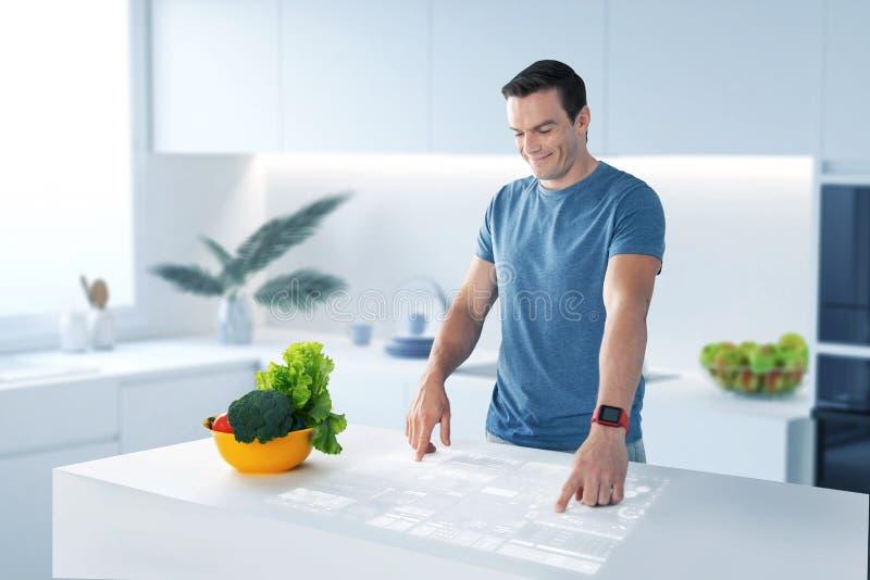 Nutricionista alegre que sorri e que toca na imagem holográfica imagem de stock