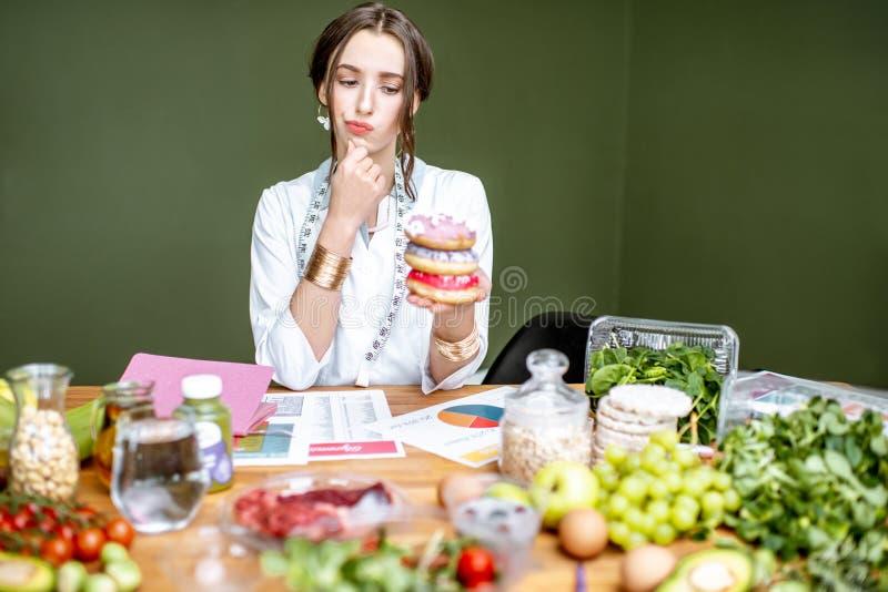 Nutricionista con la comida malsana y sana imagen de archivo libre de regalías