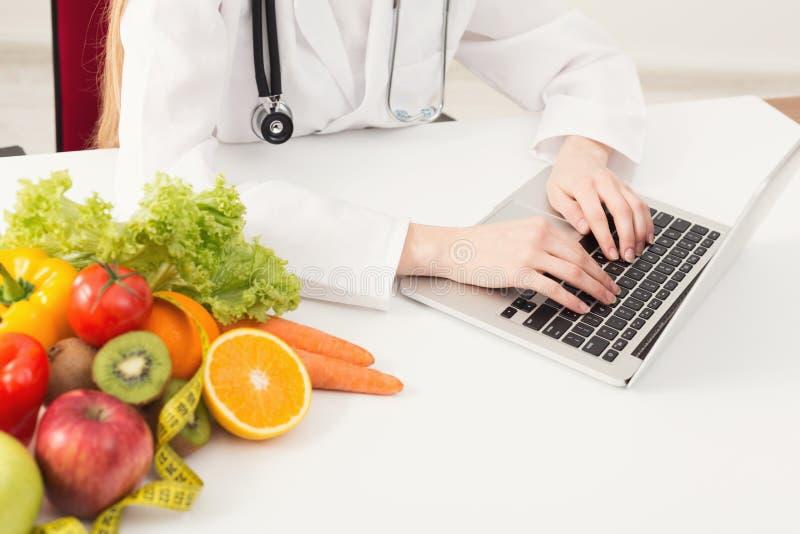 Nutricionista de sexo femenino irreconocible que trabaja en el ordenador portátil fotos de archivo