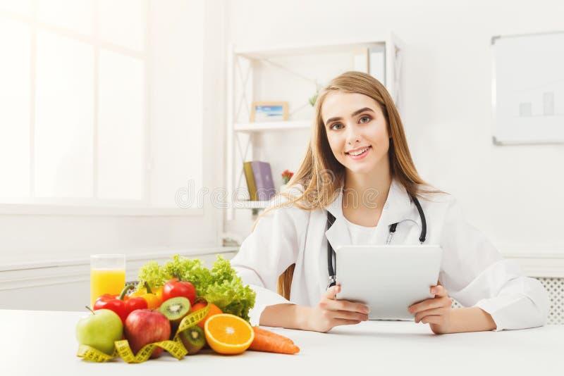 Nutricionista de sexo femenino que trabaja en la tableta digital foto de archivo