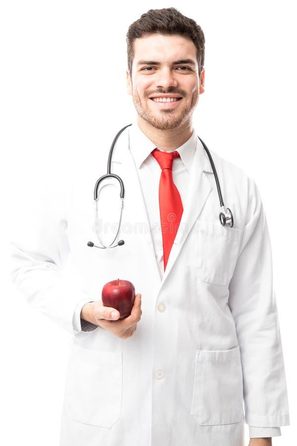 Nutricionista de sexo masculino con una manzana imagen de archivo